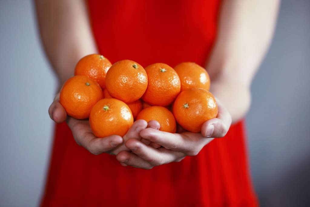 Woman in red dress holding onto a bunch of oranges